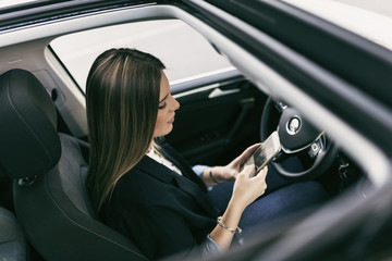 Young woman in her car driving looking smartphone and programming car with an app