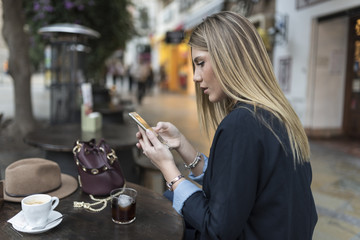 Woman looking smartphone in bar terrace while drinking coffee and coke