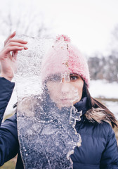 Woman looks through ice plate.