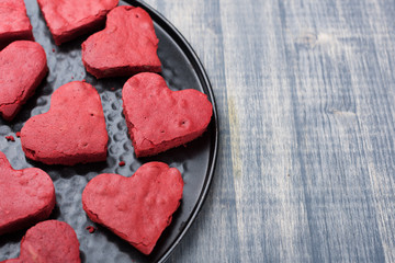 Red velvet heart cookies on plate. Baking tray with sweet biscuit cakes. Valentine days food