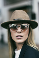 Woman with sunglasses and hat looking at camera in head shot image