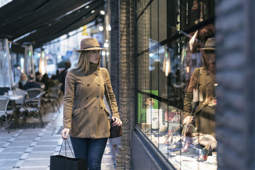 Elegant woman with raincoat and hat walking in the street and looking clothes store boutiques showcase
