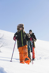 Family snowshoeing in natural scenery in winter