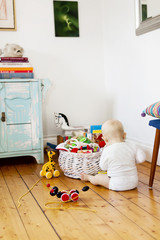 Baby playing with toys on wooden floor