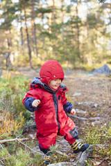 Little baby boy in red snowsuit walking in forest