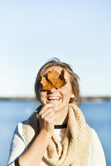 Cheerful young woman covering eyes with maple leaf
