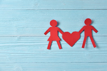Red paper people holding heart on blue wooden background.