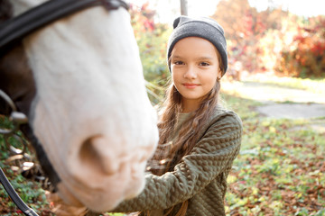 Portrait of beautiful girl with a chestnut pony