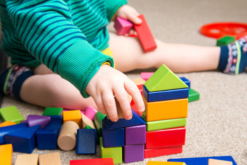 Child playing with building blocks learning new skills