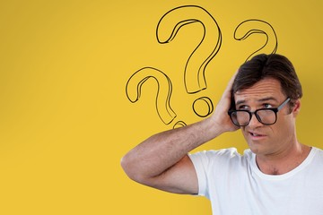 Confused man with glasses holding his head on yellow background