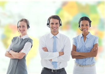 Travel agents wearing headsets in front of world map