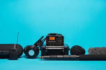 equipment for field audio recording on blue background. Windshield, microphone, radio system, boompole, recorder, portable case and headphones