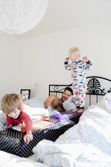 Father with two sons playing in bed