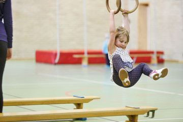 Girl hanging on gymnastic rings in gymnasium