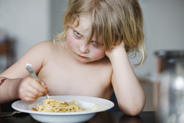 Boy eating spaghetti at dining table