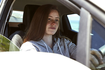 Portrait of young woman with freckles driving car