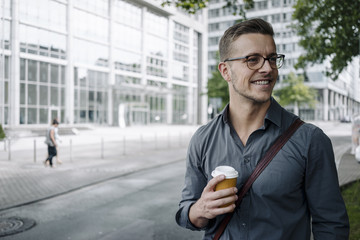 Portrait of smiling young businessman with coffee to go