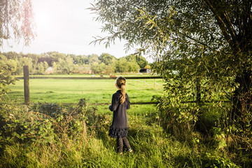 Rear view of girl standing at a field