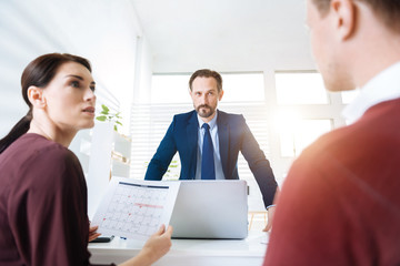 Angry boss. Beautiful sad woman looking at the colleague while male boss frowning and standing near table