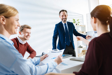 Your idea. Pretty confident male colleague  conducting presentation while  standing and laughing