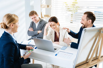Stressful day. Cheerful merry four colleagues laughing while woman touching her forehead and man putting hand on her shoulder