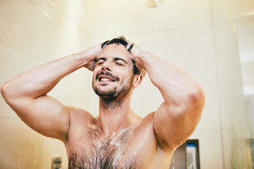 Handsome athletic young man taking shower in the bathroom