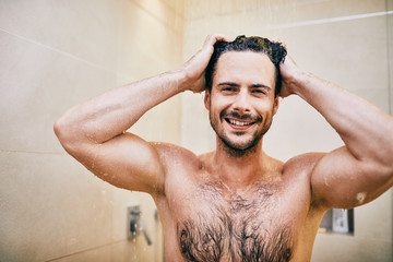 Portrait of athletic young man smiling and looking at camera while standing in the shower