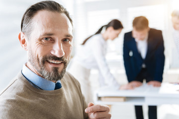 White smile. Portrait of charming sincere male colleague smiling and looking at the camera while standing on the blurred background