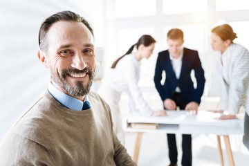 Business growth. Appealing happy male colleague grinning while posing on the blurred background and gazing at the camera