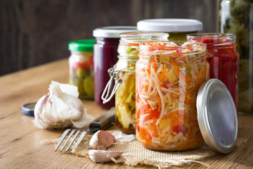 Fermented preserved vegetables in jar on wooden table. Copyspace