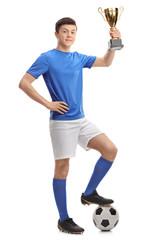 Teenage soccer player holding a golden trophy