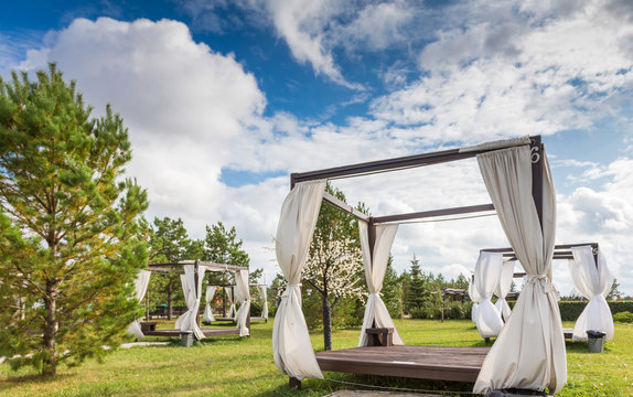 Summer wooden gazebo with a white cloth in the garden