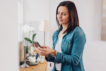 Casual woman relaxing at home with a mobile