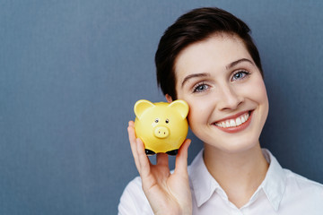 Young smiling woman holding piggy bank