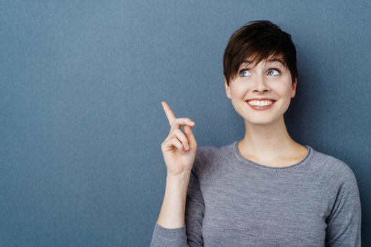 Studio shot portrait of cheerful woman pointing up