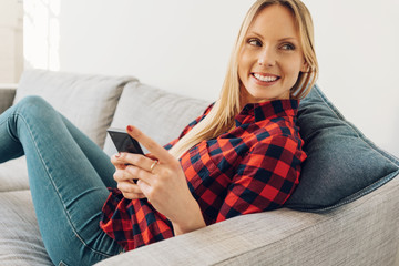 Young smiling blonde woman using phone on sofa