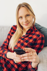 Young cheerful blonde woman using phone on sofa