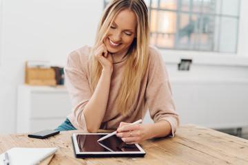 Smiling blonde woman using digital tablet