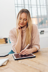 Young blonde woman using digital tablet