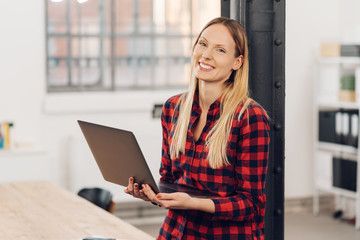 Smiling happy woman holding an open laptop