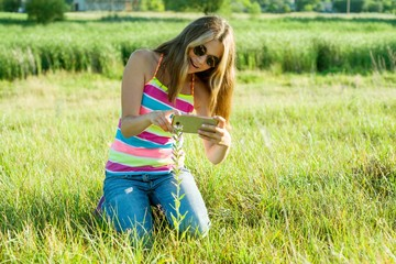 Young teenage girl using a smartphone, photographing a flower in