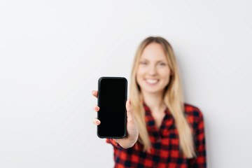 Woman holding out a mobile phone with blank screen