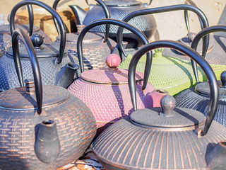 Pink and green vintage asian teapots amongst other ancient bronze teapots