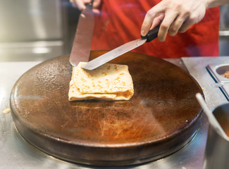 Preparation of pancake. Cook works in the kitchen.