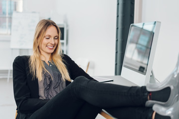 Smart businesswoman with her feet on the desk