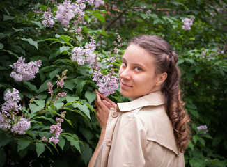 Young girl is standing near a blooming lilac bush and looking at camera.