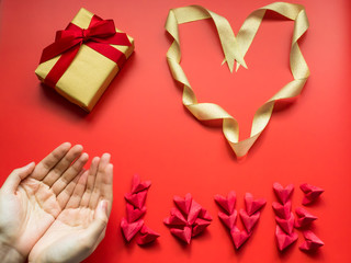 flat lay minimal concept for valentine's day and chinese new year event with beauty girl hand with love and heart symbol on red background