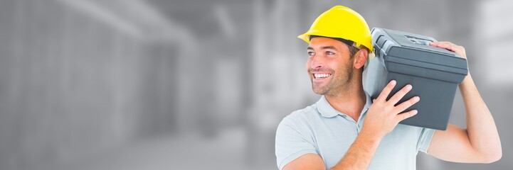 Construction Worker on building site holding toolbox