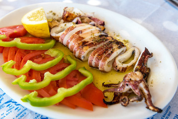 Seafood, grilled calamari served with tomatoes, green peppers and lemon in traditional Greek tavern. Naxos island. Greece.