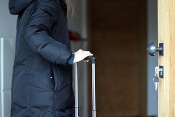 Frau mit Gepäck an der Haustür